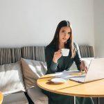Uma jovem rapariga bonita está sentada num café, a trabalhar num computador e a comunicar em redes sociais.
