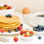 Conjunto de pequeno-almoço saudável com Panqueca e Granola com mirtilo e morango e café preto , Leite e sumo de Laranja