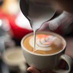 Mão de barista a fazer café com leite ou cappuccino a verter leite a fazer latte art