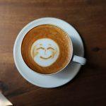 Taça de cappucino quente e saboroso com um sorriso de latte de arte.